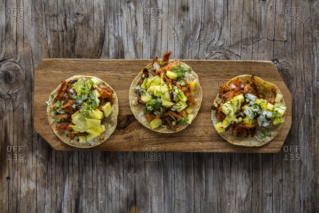 Overhead view of al pastor taco with pineapple, coriander and onion over a wooden background