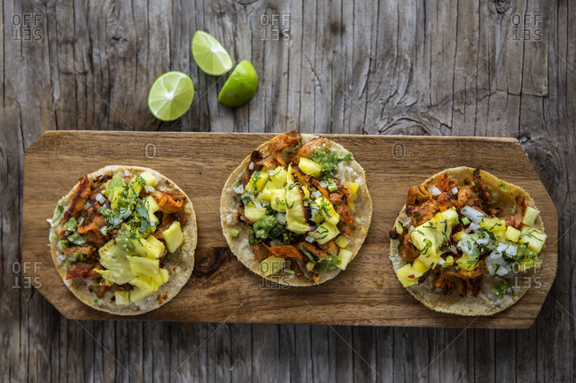 Overhead view of al pastor taco with pineapple, coriander, lemon and onion over a wooden background