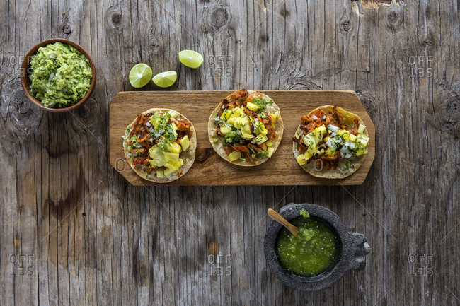 Overhead view of al pastor taco with pineapple, coriander, lemon, onion and lemon water over a wooden background