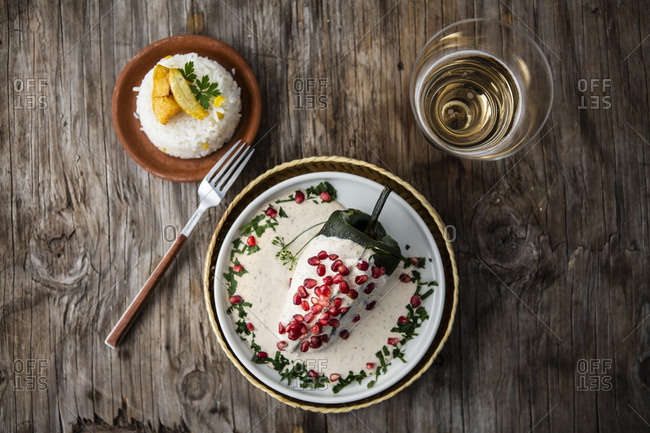 Overhead view of chile in nogada with cream, pomegranate, rice, banana and white wine over a wooden background