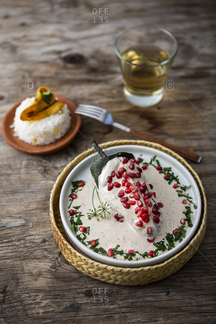 View of chile in nogada with cream, pomegranate, rice, banana and white wine over a wooden background