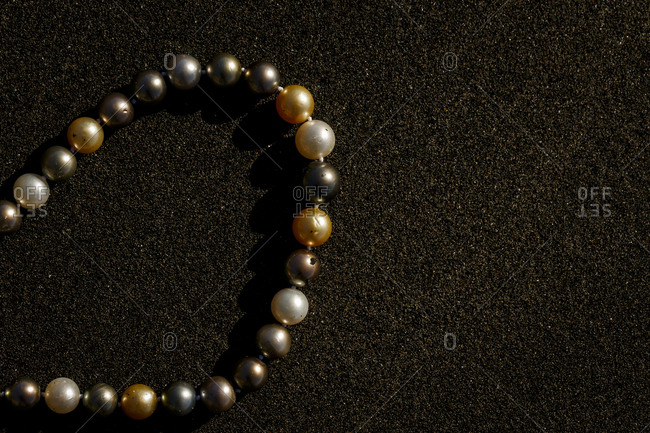 Black and gold pearls laying on black sand.