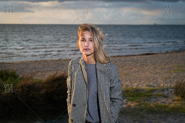 Blonde woman wearing plaid jacket on windy beach at sunset