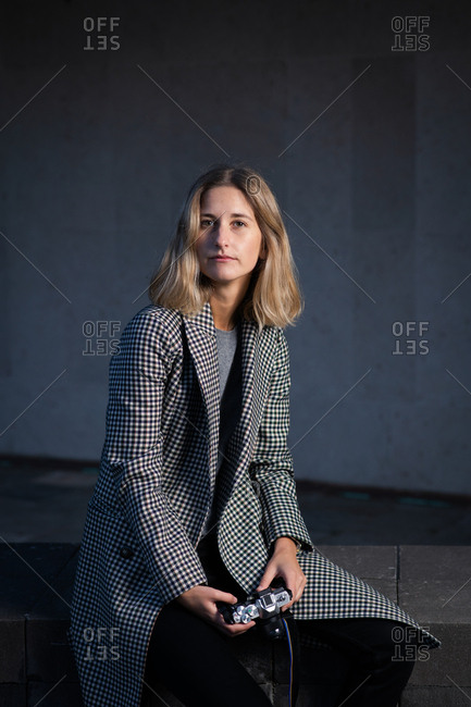 Blonde woman wearing plaid jacket sitting on concrete wall holding camera