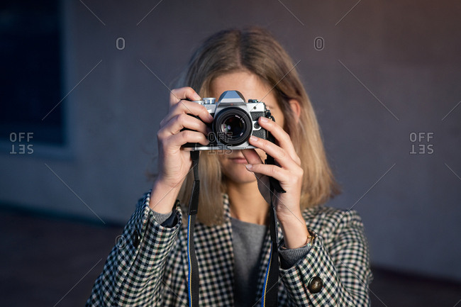 Blonde woman taking photograph with a 45mm camera