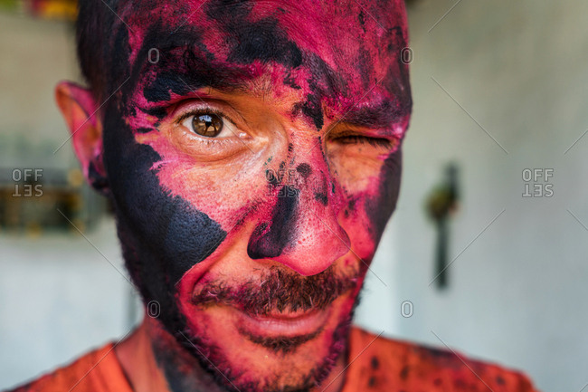 Close up of a man with his face painted in pink and black at the Holi Festival celebration in Hampi, Karnataka, India