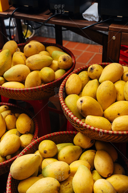 Baskets filled with yellow mangos in a market