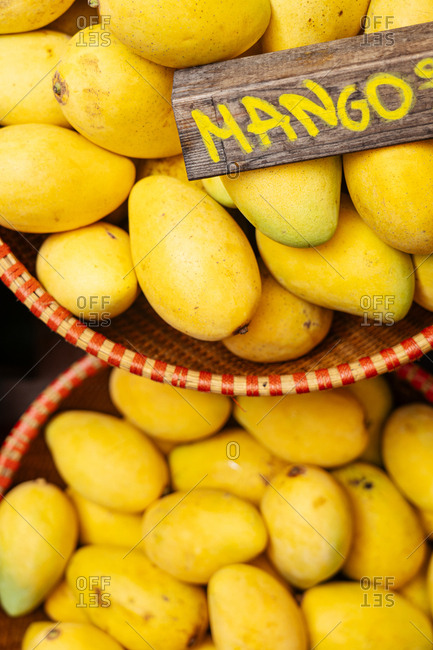 Overhead view of baskets filled with yellow mangos in a market with sign