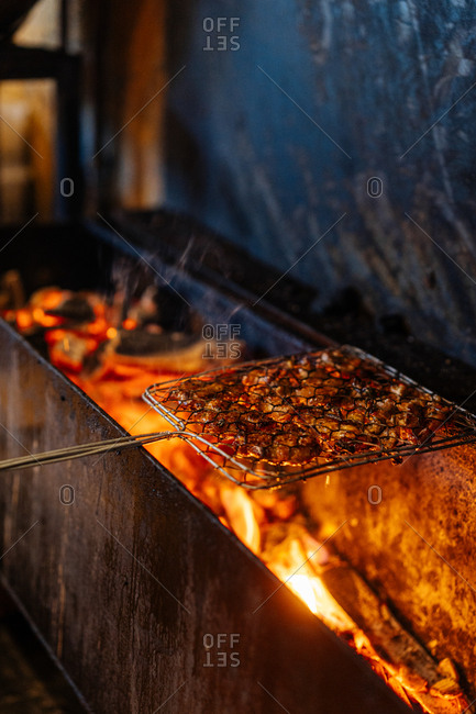 Meat being cooked over fire grill in a market
