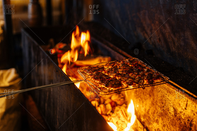 Close up of meat being cooked over fire grill in a market