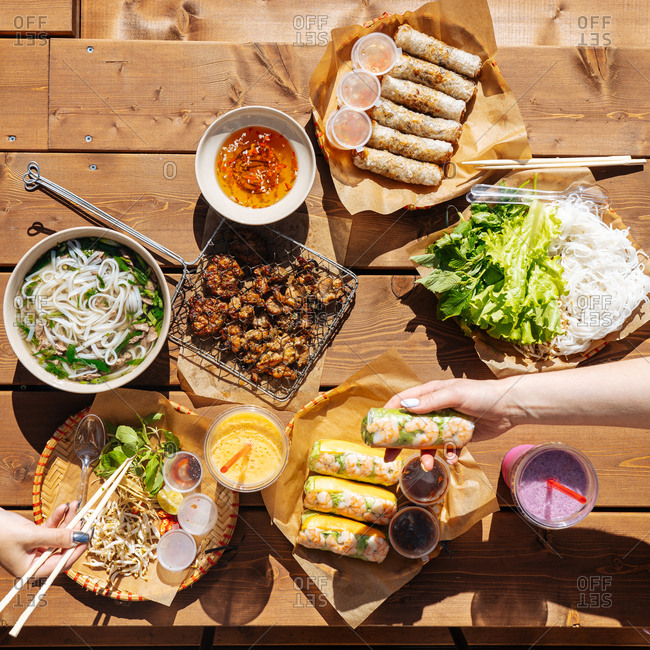 Overhead view of two woman eating Asian meal on outdoor table