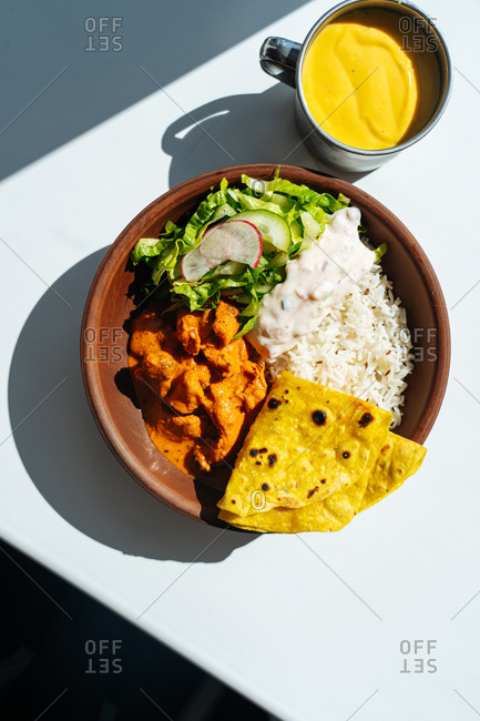 Overhead view of a curry dish with rice and salad