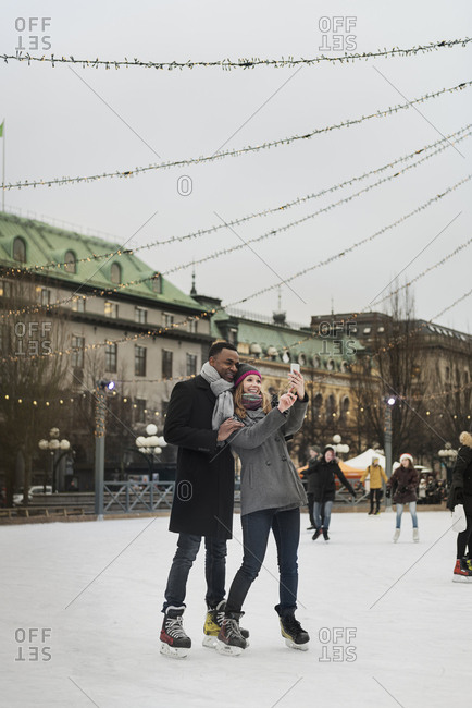 Couple taking selfie while ice skating