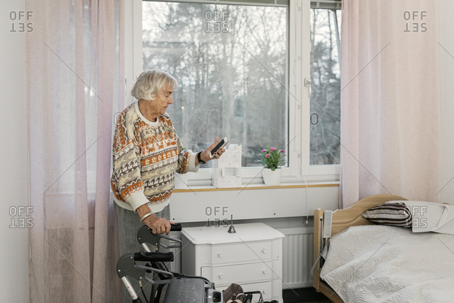 Senior woman using smart phone by window