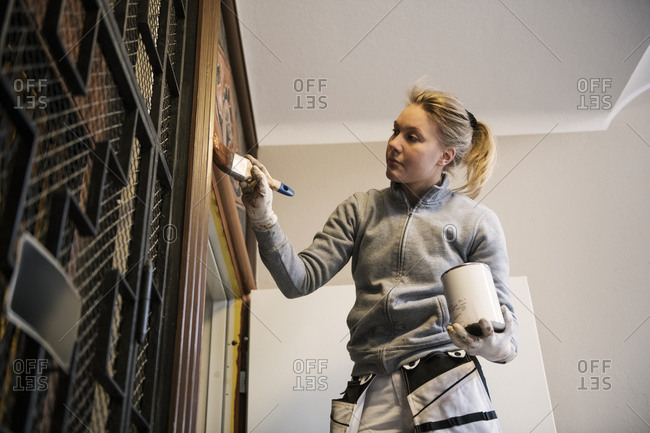 Painter painting door in apartment building