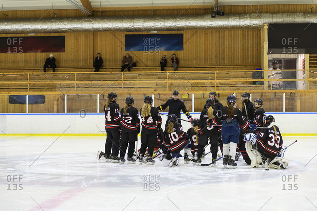 Girls listening to their coach during ice hockey training