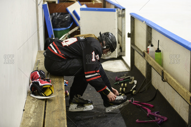 Girl in ice hockey uniform tying laces on ice skates