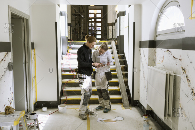 Painters using smart phone in apartment hallway