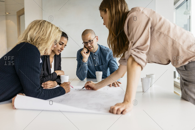 Businesspeople looking at plans during meeting
