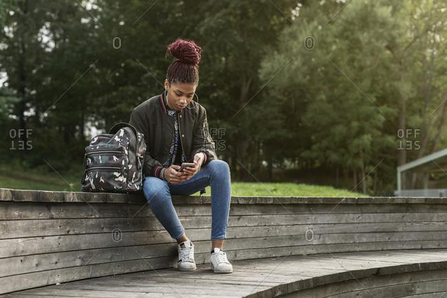 Teenage girl using smart phone in park