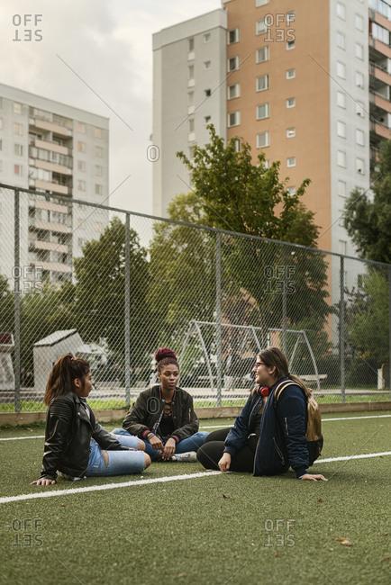 Teenage girls sitting on tennis court