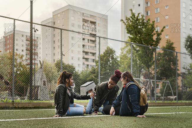 Teenage girls using smart phone on tennis court
