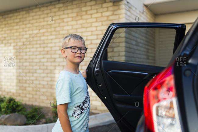 Boy by open car door