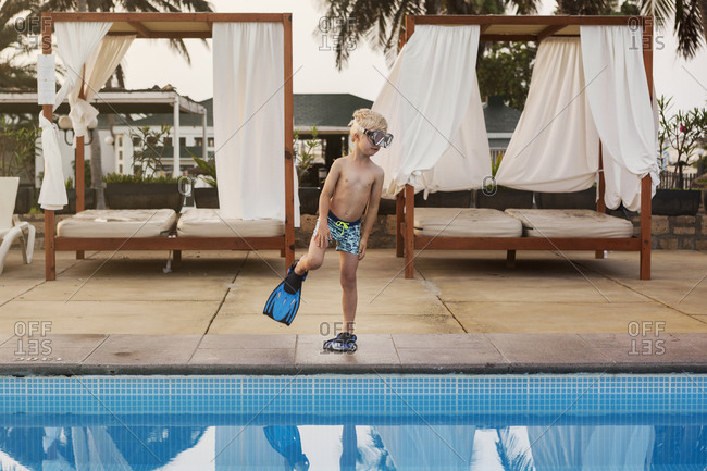 Boy standing poolside
