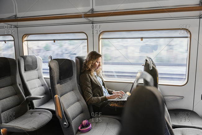 Young woman commuter on train using laptop