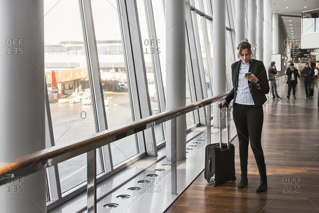 Woman with suitcase and smart phone in airport