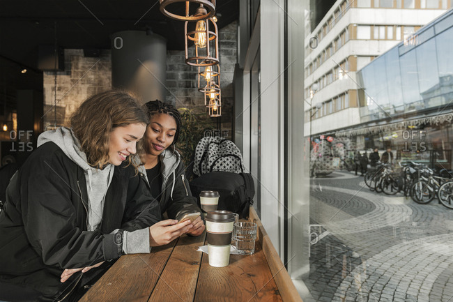 Teenage girl using smart phone in cafe