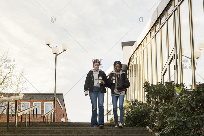 Teenage girls with coffee cups on staircase