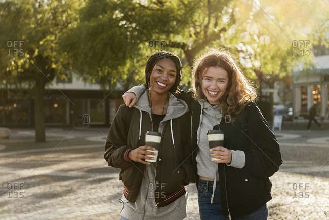 Smiling teenage girls with coffee cups