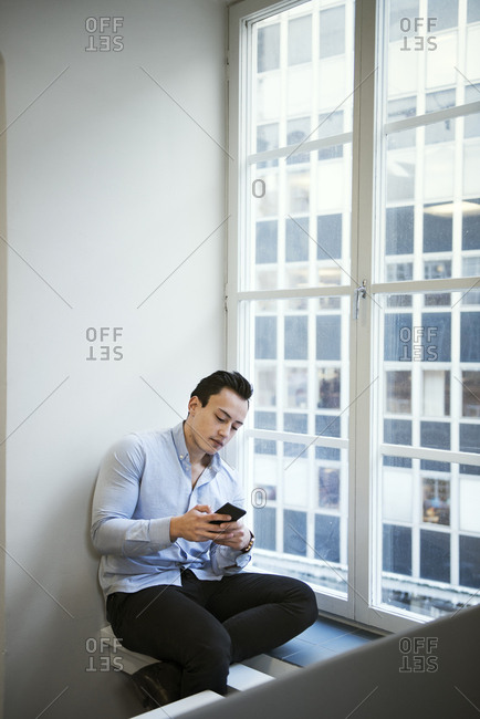 Young man using smart phone by window
