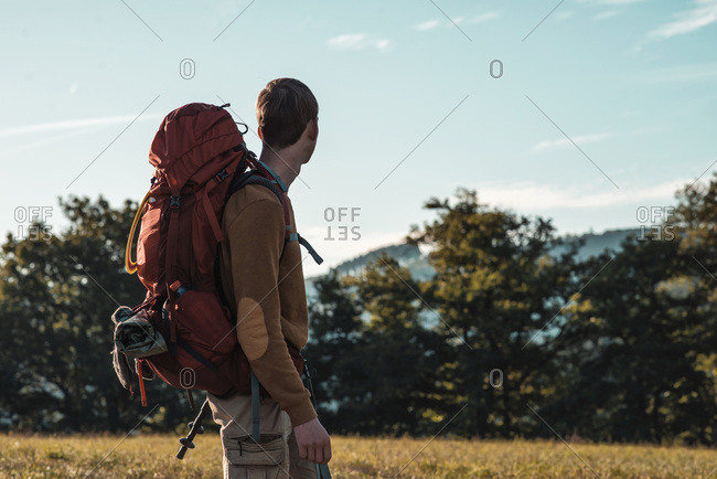 Young man hiking with large backpack looking out at mountain landscape