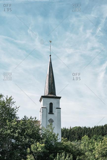 Tall clock tower under cloudy blue sky