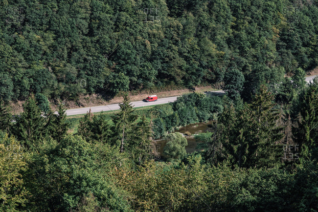 Elevated view of a red van driving on highway in a dense green forest