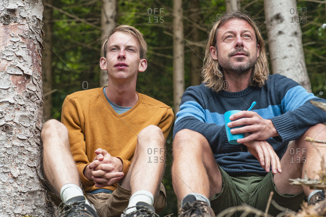 Two men sitting in forest relaxing and taking in the view