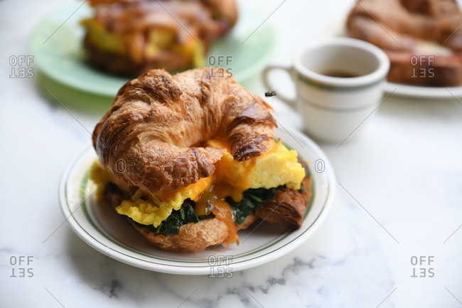 Breakfast croissant sandwich on marble surface
