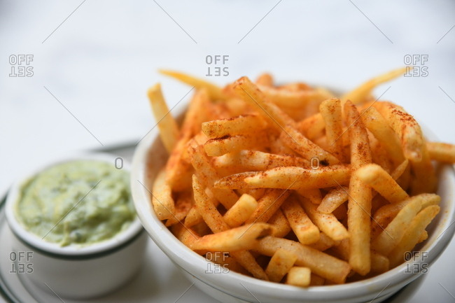 Close up of seasoned French fries with dipping sauce on marble surface