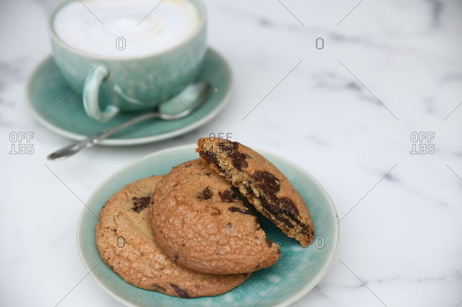 Fresh baked chocolate chip cookies with a cappuccino