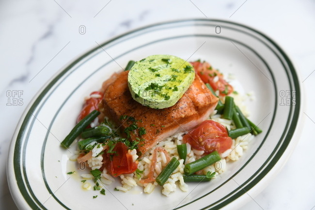 Salmon on a bed of rice with vegetables