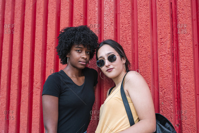 Cheerful multiracial friends standing in front of red wall