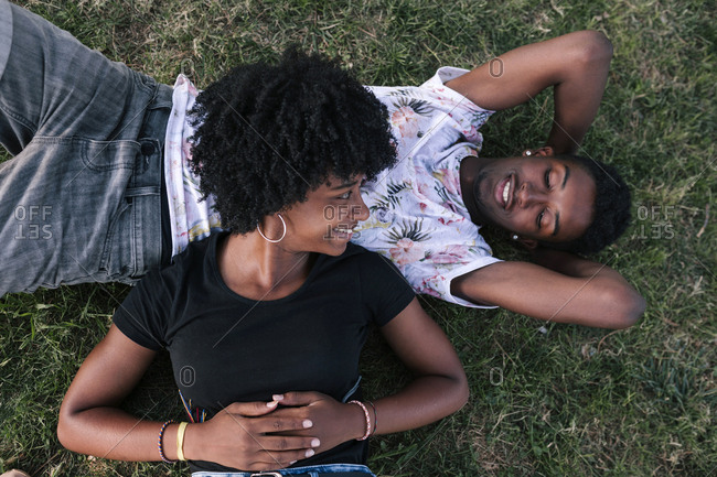 Black couple lying on the grass together
