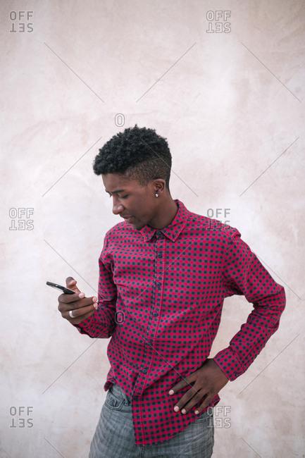 Black teenage boy typing on his mobile phone