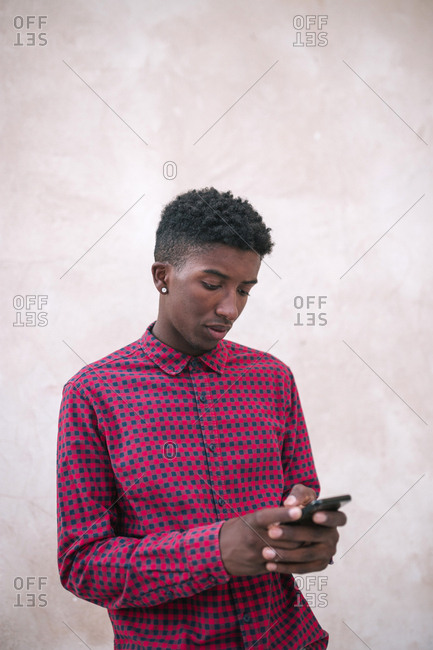 Black teenage boy sending text message on his mobile phone