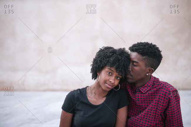 Black couple sitting close together in the city