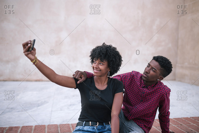 Black couple taking a selfie in the city