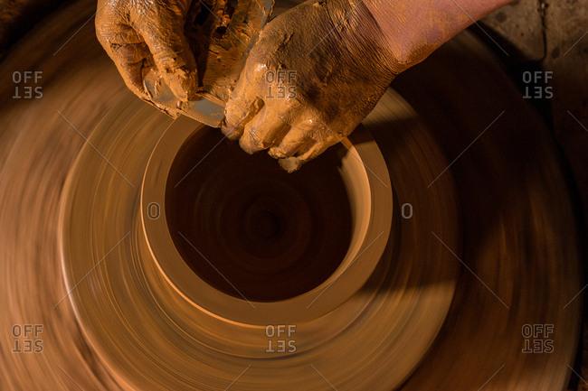 Hands making ceramic art