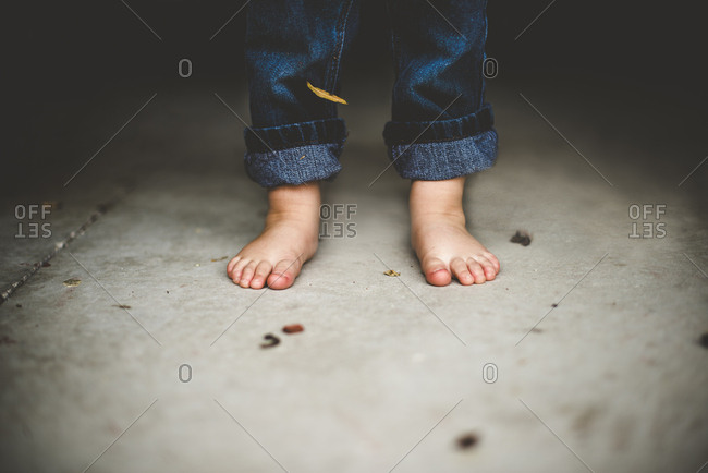 Barefoot toddler boy in jeans standing on concrete